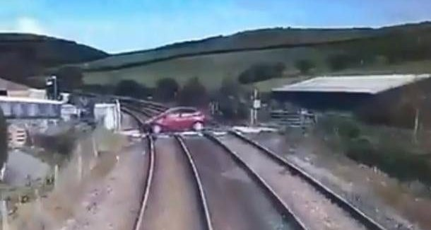 This shocking footage shows the moment an idiot driver came within seconds of being crushed by a fast-moving train after not looking both ways at a crossing (Video)